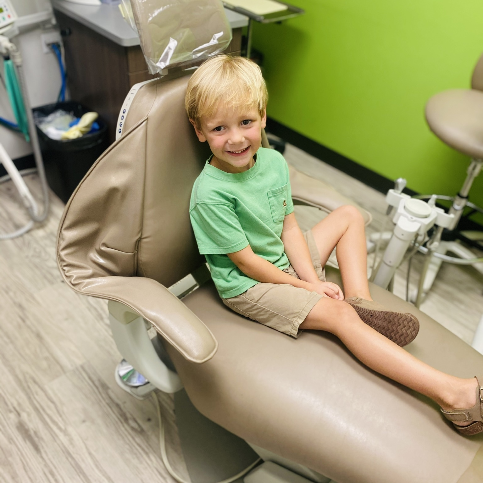 Child sitting in dental chair south Mississippi smiles